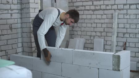 клейкий : worker in work wear laying block and checking it with bubble level Стоковые видеозаписи