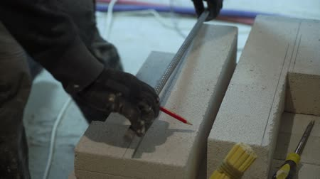 armature : construction worker marking aerated concrete block for armature cutting Stock Footage