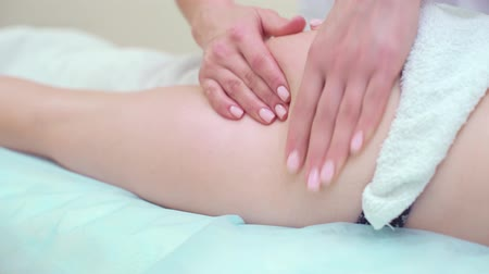 therapeutic : female hands massaging buttocks of young woman closeup