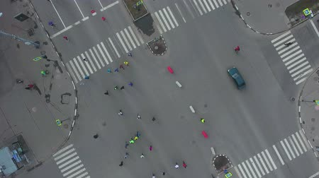 run down : aerial top down shot of city road intersection with people running at marathon Stock Footage