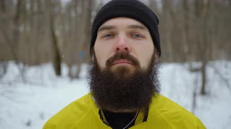 bigode : closeup of hipster man with blue eyes and beard standing in winter forest