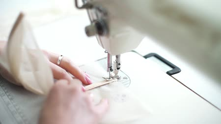 punto maglia : closeup of woman hands with manicure stitch pieces of fabric on sewing machine