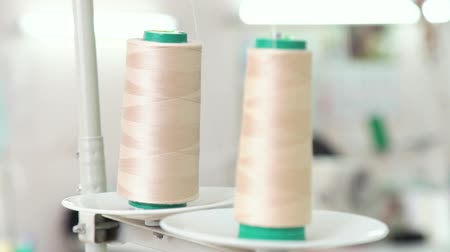 akrilik : closeup rack focus on skeins of thread on industrial sewing machine Stok Video