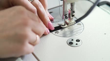 stiksel : closeup of seamstress hands with manicure stitching fabric on sewing machine