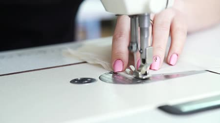 ручная работа : closeup of female seamstress hands sewing fabric on sewing machine Стоковые видеозаписи