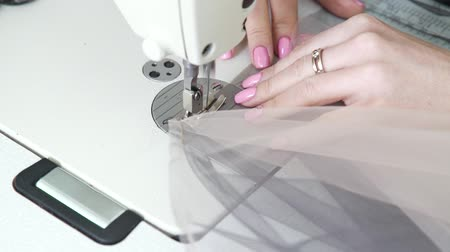 вязание : closeup of seamstress hands sewing pieces of fabric on sewing machine
