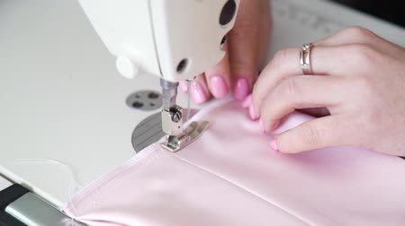 punti maglia : closeup of female hands with manicure sewing fabric on sewing machine
