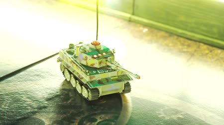 remotely : radio controlled scale model tank with camouflage moving on play board