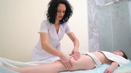 coxa : professional masseur massaging young woman thighs in spa salon Stock Footage