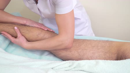 masszőr : female hands doing relaxing massage on male unshaven leg in spa salon