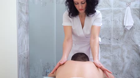 mimos : beautiful female therapist doing relaxing massage on male back in spa salon Stock Footage