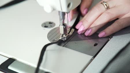 вязание : closeup of accurate hands of female seamstress sewing fabric with sewing machine