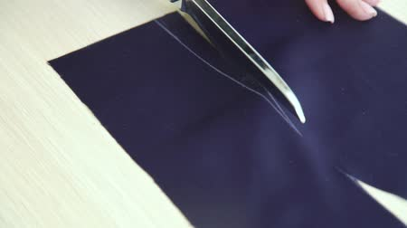 ручная работа : closeup of beautiful hands of young woman cutting fabric with scissors