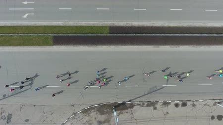 run down : aerial of many people running at sports race marathon on the roads of city