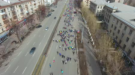 run down : aerial shot of city marathon runners running on empty road