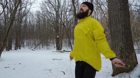 skákání : bearded sporty man jumping with skipping rope in winter forest Dostupné videozáznamy