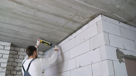 szigetelés : builder filling gap between wall and ceiling with mounting foam