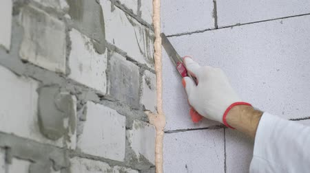 монтаж : tilt down closeup of builder hand removing excessive mounting foam between walls