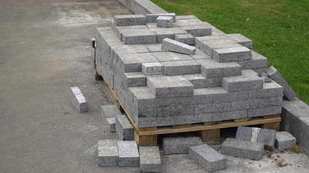 godo : pile of paving stones lie on wooden pallet near green lawn