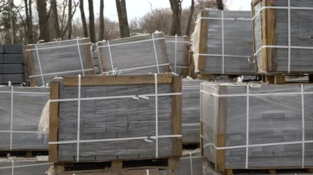 godo : paving stones packed in stacks and wrapped in film are stored on ground outdoors Vídeos