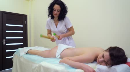 masszírozó : young woman getting anti cellulite massage with bamboo sticks in spa salon