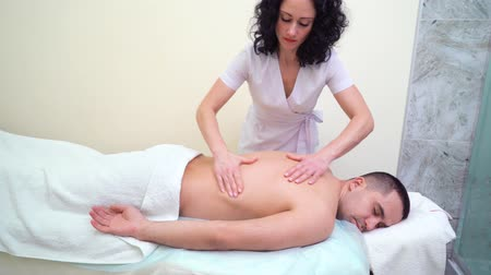 masszőr : young attractive female therapist massaging back of male customer in spa salon Stock mozgókép