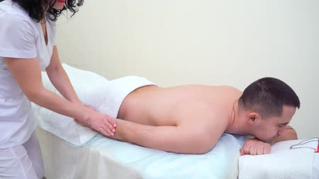 masszőr : beautiful female therapist massaging arm of male customer in spa salon