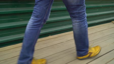 rebuild : low shot of man feet walk on wooden deck beside metal fence at construction site