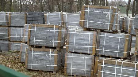 мощение : arc shot of paving stones packed in stacks stored on ground outdoors