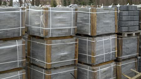 valoun : pan shot of stacks of paving stones wrapped in construction film stored outdoors