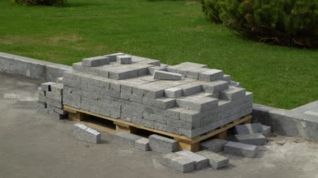 valoun : arc shot of pile of grey paving stones on wooden pallet near lawn in city park