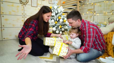 uitpakken : happy family with toddler daughter unpacking Christmas presents at home