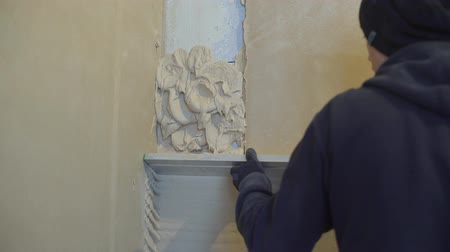 leveling : construction worker leveling plaster on wall at renovation site Stock Footage