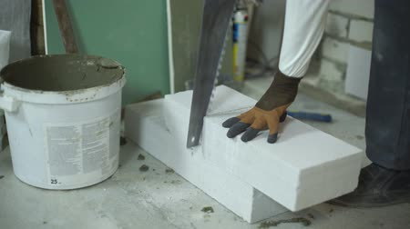 aerated : view of builder hands cutting aerated concrete block with hand saw