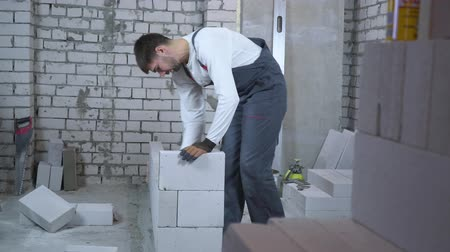 aerated : young builder laying aerated concrete block and checking it with bubble level