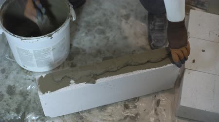 aerated : high angle shot of builder hands putting mortar on block sides with spatula