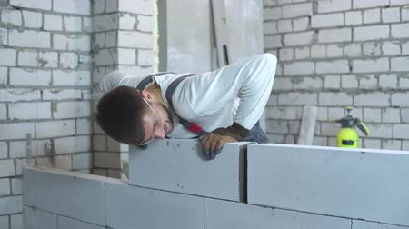 aerated : cheerful young builder in work wear laying blocks at construction site