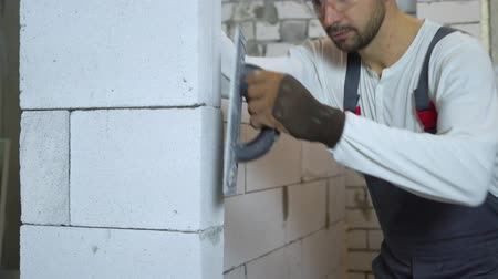 aerated : tilt shot of young builder in work wear grinding block wall with abrasive tool