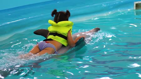 dolphin : little girl gets dolphin assisted therapy in dolphinarium