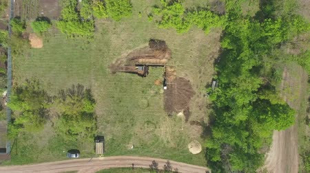verhuizer : aerial of industrial machines digging foundation pit for new house Stockvideo