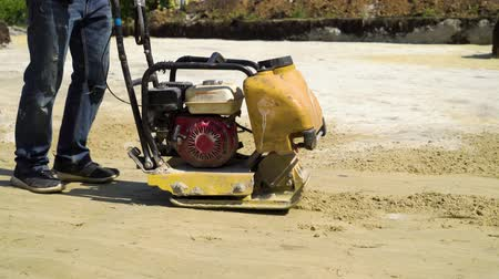 compactor : low shot of man ramming sand surface with vibratory plate compactor