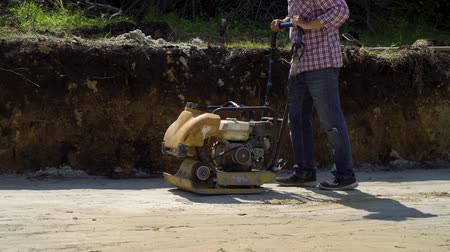 kompakt : low shot of worker using vibrating rammer on sand surface Stok Video