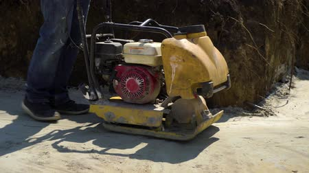 compactor : partial shot of man working with vibrating plate compactor on sand surface Stock Footage