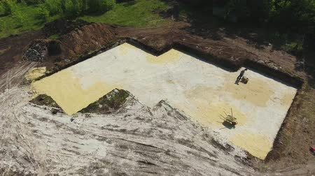 kompakt : aerial of worker using vibrating rammer in foundation pit of new house