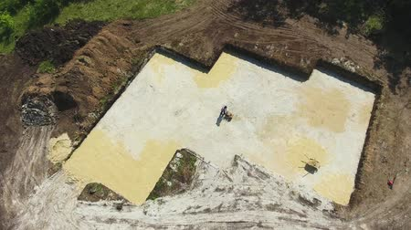 compactor : aerial of man ramming surface with vibratory plate compactor in foundation pit