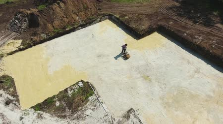 compactor : aerial of man working with plate compactor in foundation pit of new house