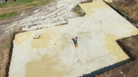kompakt : aerial of worker ramming sand surface with vibratory plate compactor in pit Stok Video
