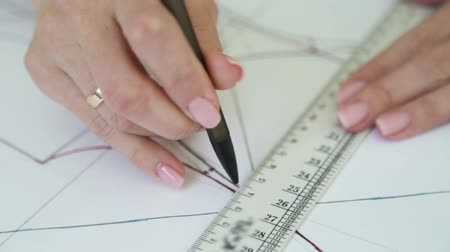 couturier : closeup rack focus of married woman hands drawing sewing pattern on paper Stock Footage