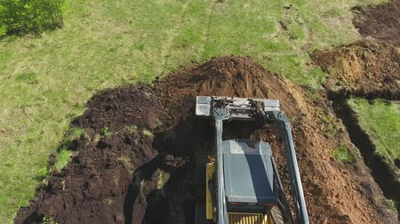 травянистый : aerial of bulldozer and excavator digging foundation pit on grassy field Стоковые видеозаписи