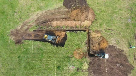 травянистый : top down of bulldozer and excavator digging pit according to marking on ground
